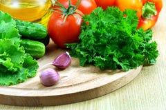 Verduras frescas para la ensalada en una tarjeta de corte foto de archivo libre de regalías