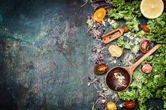Verduras frescas que cocinan los ingredientes con col rizada, el limón y los tomates en el fondo rústico, visión superior Imágenes de archivo libres de regalías