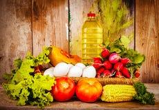 Verduras frescas, huevos y una botella de aceite en una cesta Imágenes de archivo libres de regalías