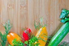 Verduras frescas y una tabla de cortar, visión superior Foto de archivo