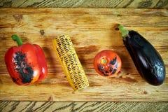 Verduras fritas en una parrilla y apiladas en un jpg de la tabla de cortar fotografía de archivo