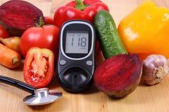 Verduras, glucometer y estetoscopio en la superficie de madera, forma de vida sana, nutrición, diabetes foto de archivo