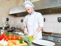 Verduras masculinas del corte del cocinero para la comida de la ensalada Foto de archivo