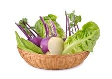 Verduras mezcladas, colinabo, quingombó, bebé lechuga romana en cesta en blanco Imagenes de archivo