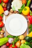 Verduras orgánicas alrededor de la placa blanca con el cuchillo y la bifurcación Fotos de archivo libres de regalías