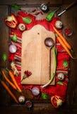 Verduras orgánicas frescas alrededor de la vieja tabla de cortar con la cuchara de madera en servilleta rústica y el fondo de mad Foto de archivo