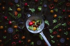Verduras orgánicas frescas en colador de la cocina Guisantes verdes, bróculi, tomate y rábano en la tabla de madera Visión superi foto de archivo