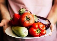 Verduras orgánicas frescas en manos del ` s del hombre Fotografía de archivo