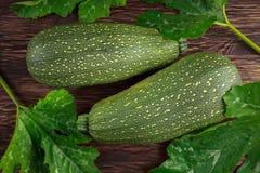 Verduras orgánicas recientemente escogidas crudas del calabacín del tuétano con las hojas en la tabla de madera Imágenes de archivo libres de regalías