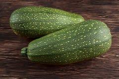 Verduras orgánicas recientemente escogidas crudas del calabacín del tuétano con las hojas en la tabla de madera Fotos de archivo