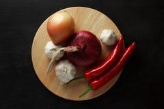 Verduras pimienta roja, cebollas y ajo en un soporte de madera Visión desde arriba Imagen de archivo libre de regalías
