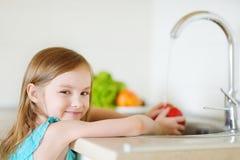 Verduras que se lavan de la niña adorable Fotografía de archivo libre de regalías