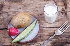 Verduras sanas de la comida en un plato y una leche, aún vida Foto de archivo libre de regalías