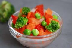 Verduras sanas del vegano colorido congelado Brocolli, zanahorias, guisantes, pimienta Imagen vertical Fondo gris fotos de archivo