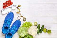 Verduras sanas frescas, zapatillas de deporte en el fondo de madera blanco Foto de archivo libre de regalías