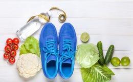 Verduras sanas frescas, zapatillas de deporte en el fondo de madera blanco Fotografía de archivo