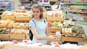 Verduras shopaholic de una investigación de la persona 20s en mercado metrajes