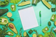 Verduras verdes con un cuaderno para la inscripción Para preparar una comida sana y sana El cocinar verde sano del vegano fotos de archivo libres de regalías
