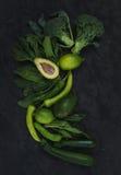 Verduras verdes crudas fijadas Bróculi, aguacate, pimienta, espinaca, zuccini y cal en fondo de piedra oscuro Imagen de archivo libre de regalías