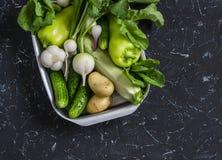 Verduras verdes y blancas frescas - pepinos, pimientas, rábano, rábano, ajo, cebolla, patata, calabacín en un fondo oscuro Foto de archivo libre de regalías