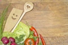 Verduras y artículos de cocina en tabla de cortar Foto de archivo libre de regalías