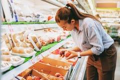 Verduras y frutas sanas de la comida de las mujeres que hacen compras asiáticas en supermercado imagen de archivo libre de regalías