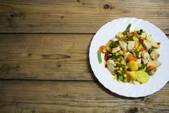 Verduras y pechuga de pollo en la tabla de madera imagen de archivo