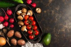 Verduras y setas variadas en un plato de cerámica rústico El concepto de consumición sana Fondo del marrón oscuro, visión superio Foto de archivo libre de regalías