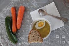 Verduras y un cuenco de sopa con la cuchara fotografía de archivo