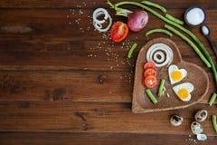 Verduras y una placa con los huevos fritos en lanzamiento ascendente del fondo del cierre de madera de los gastos indirectos imagen de archivo libre de regalías