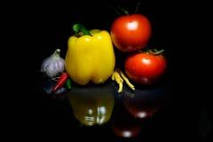 Verduras y una reflexión de las pimientas de los tomates del fondo de la oscuridad Foto de archivo libre de regalías