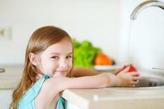 Verdure adorabili di lavaggio della ragazza in una cucina Fotografie Stock