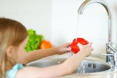 Verdure adorabili di lavaggio della ragazza in una cucina Fotografia Stock Libera da Diritti