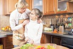 Verdure adorabili di taglio della figlia e della madre per insalata Togethe Immagine Stock