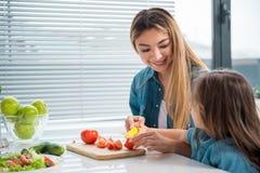 Verdure allegre di taglio della madre insieme al suo bambino immagine stock