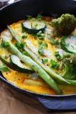 Verdure arrostite ed uova rimescolate in una padella Fotografia Stock