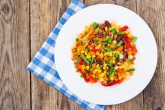 Verdure bollite in piatto bianco sulla vecchia tavola di legno La VE in buona salute fotografia stock libera da diritti