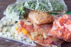 Verdure congelate sul tagliere e sacchetti di plastica su un di legno Fotografia Stock
