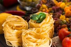 Verdure crude e mature della pasta, limone su un fondo di legno Ingredienti per la cottura dei piatti italiani Primo piano Immagine Stock