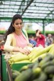 Verdure d'acquisto della giovane donna sul mercato Immagine Stock