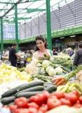 Verdure d'acquisto della giovane donna sul mercato Fotografie Stock
