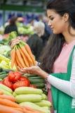 Verdure d'acquisto della giovane donna sul mercato Immagini Stock Libere da Diritti