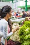 Verdure d'acquisto della giovane donna sul mercato Fotografia Stock Libera da Diritti