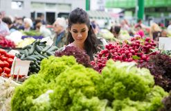 Verdure d'acquisto della giovane donna sul mercato Fotografie Stock Libere da Diritti