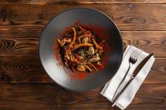 Verdure del wok con le spezie in una banda nera immagine stock