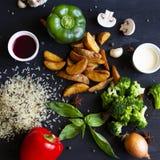 Verdure di estate su fondo di legno nero Riso del peperone verde e rosso dei broccoli e patate fritte immagini stock libere da diritti
