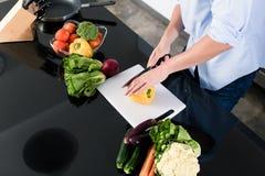 Verdure di taglio dell'uomo in cucina Immagine Stock Libera da Diritti