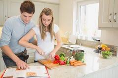 Verdure di taglio della donna con l'uomo che legge il libro di cucina Immagini Stock