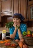 Verdure di taglio della donna nella cucina Immagini Stock
