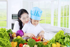 Verdure di taglio della madre e del ragazzo immagine stock